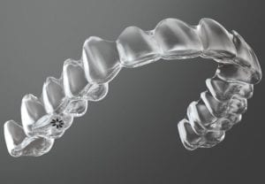 Photo of an upper Invisalign aligner against a dark gray background.