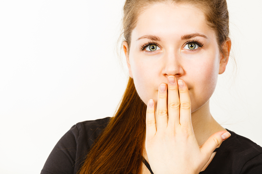 Woman covering her mouth with hand. Seeing something shocking surprised and speechless face expression.