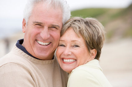 Older couple holding each other and smiling in a pose