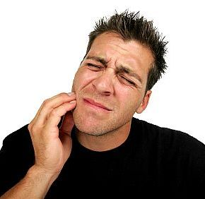 man holding his jaw in pain in need of a dentist